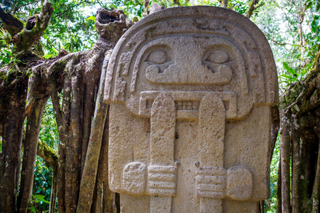 A mysterious statue of a male person  stands in the rainforest next to an old tree with large roots. The statues of San Agustin are a mystery to historians - San Agustin, Colombia in December 2015