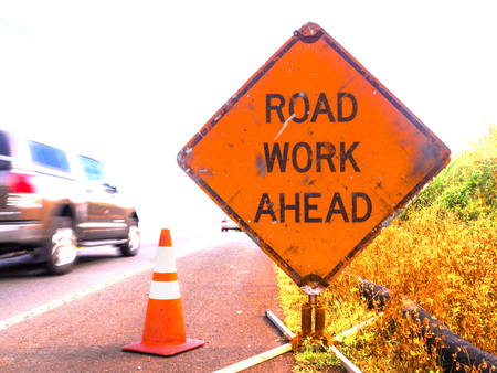 A sign reading Road Work Ahead is passes by a fast car