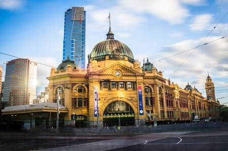 flinders: Melbournes iconic Flinders Street station with Eureka tower in the background in afternoon light.