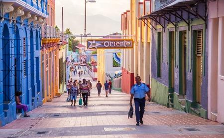 city scene: Santiago de Cuba, Cuba on January 5, 2016: Cuban people walking in the pedestrianised city centre of Santiago de Cuba