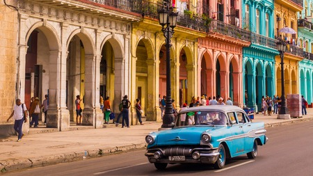 Havana, Cuba on December 22, 2015: A blue oldtimer taxi is driving through Habana Vieja in front of a colorful facade Editorial