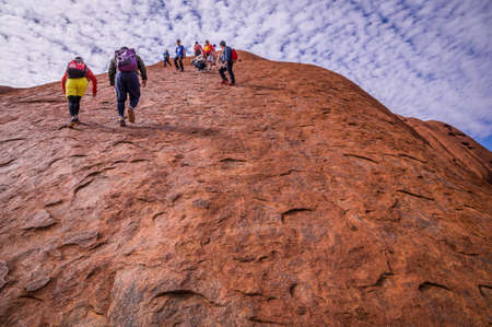 uluru: Uluru Ayers Rock, Australia on September 11, 2015: Tourists are climbimg up and down Uluru. The Anangu aborigines of Uluru ask people to respect their culture and not to dare the dangerous climb.