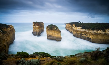 ard: Loch Ard Gorge at Great Ocean Road. This long-exposure captures the movement of waves and clouds around the beautiful landmark of orange rocks Stock Photo