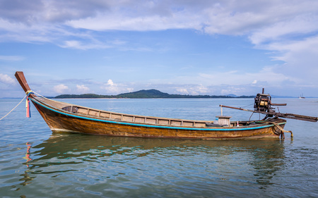 whitespace: Longtail boat waiting for passengers on beautiful Ko Lanta island, Thailand. The clouds and the boat frame a piece of blue sky a whitespace Stock Photo
