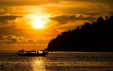 Sunset view from Pattaya beach in Ko Lipe, Thailand shows a longtail boat driving in front of the setting sun Zdjęcie Seryjne