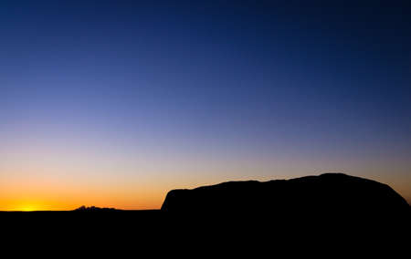 olgas: View from sunrise viewpoint of the silhouette of Uluru Ayers Rock with the sun setting behind Kata Tjuta The Olgas Stock Photo
