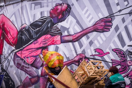 Bogota, Colombia on December 14, 2015: Wall covered in anti-capitalistic street art by artist Guache in La Candelaria neighborhood of Bogota showing a poor person bending to carry a rich person