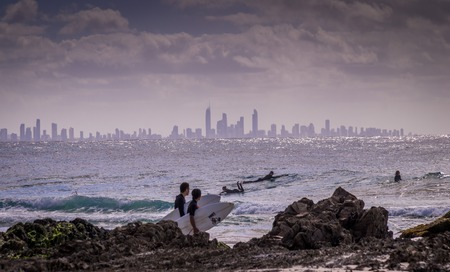 goldcoast: Surfers Paradise, Australia on August 16, 2016: Surfers enjoying the waves at snapper rocks with the skyline of Surfers paradise in the background