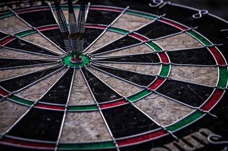 Three dart arrows hitting in the target center of dartboard