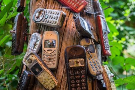 clavados: Viejos teléfonos rotos clavados en un árbol Foto de archivo