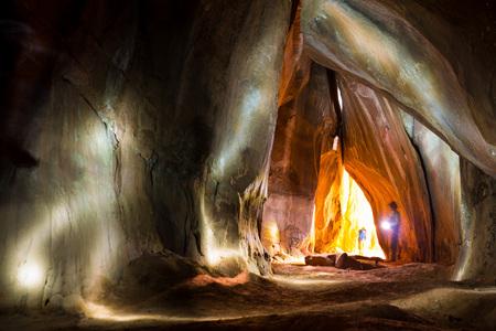 An adventurous explorer shines his torch into a dark cave in Torotoro National Park, Bolivia