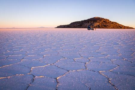 infamous: The sun rises over worlds largest salt lake Salar de Uyuni. Tourists tour Bolivias infamous salt lake on a jeep