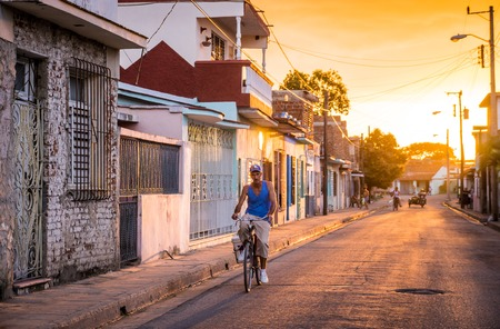 Camaguey, Cuba on January 2, 2016: Cuban man riding his bicycle through a street in the historic Caribbean city center of Camaguey at sunset Imagens - 73455540