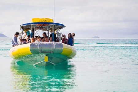 airlie: Whitehaven beach, Whitsunday Island, Queensland, Australia on August 22, 2016: Tourist speed boat in turquoise waters