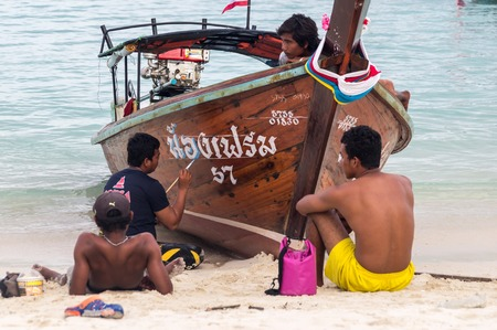Ko Lipe, Thailand on November 10, 2016: Thai men painting a longtail boat Editorial