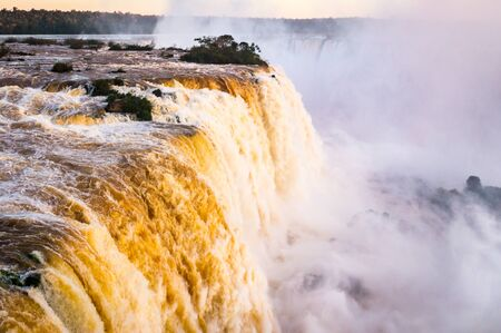 Beautiful Sunset Colors at Cataratas do Iguacu at Iguazu Falls, Foz do Iguacu, Parana State, Brazil. In the evening the Iguacu Falls in Brazil shine in beautiful warm golden hour colors.