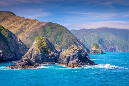 Cook Strait, New Zealand: View from the ferry that crosses between the North and the South Island entering the Marlborough Sound. The rocky cliffs tease the spectacular landscapes of the South Island.