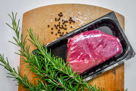 Raw beef steak in vacuum skin packaging and spices on wooden chopping board Reklamní fotografie