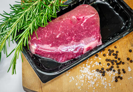 Vacuum-packed beef steak on wooden chopping board with salt, pepper and rosemary spices Reklamní fotografie