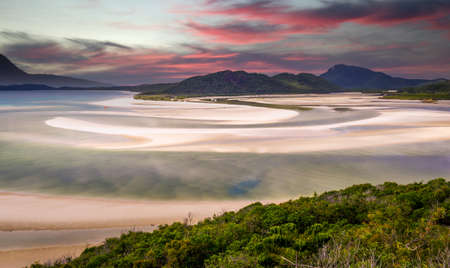 View from hill inlet lookout on Whitehaven beach at Whitsunday Island near Airlie Beach, Australia at low tide. Beautiful pink clouds stand at the sky at sunrise.