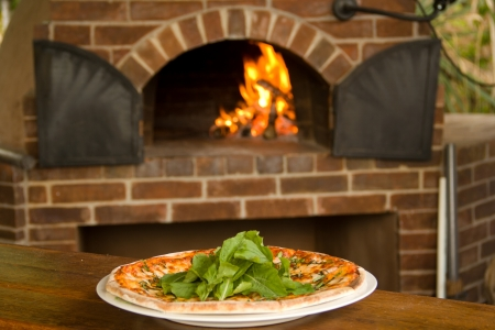 pizza oven: Pizza on a plate with pizza oven in background