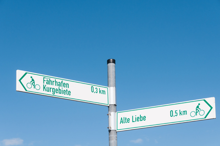decission: Signs that show the way for Alte Liebe and Faehrhafen and Kurgebiete in front of blue sky Stock Photo