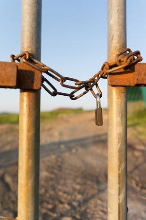 vertical format: A fence locked wirh a chain and secured by a padlock photographed in vertical format