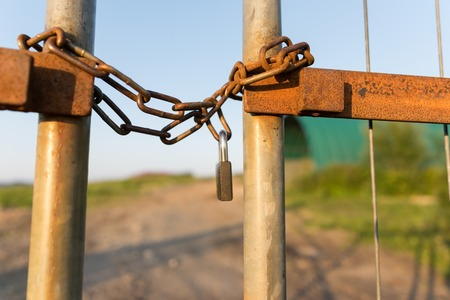 horizontal format: A fence locked wirh a chain and secured by a padlock photographed in horizontal format