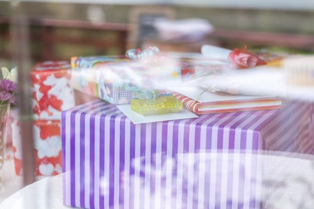 windowpane: A table with gifts and birthday presents behind a windowpane wirh refelctions  in the glass