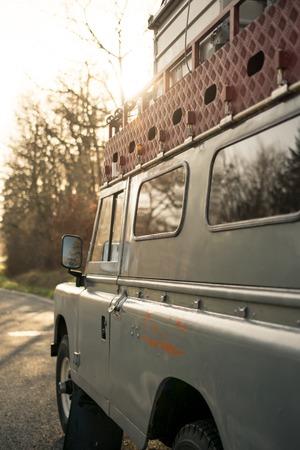 descubridor: Cara de un cuatro por cuatro vehículos todoterreno Oldtimer al atardecer con luz dorada y reflexiones en la ventana