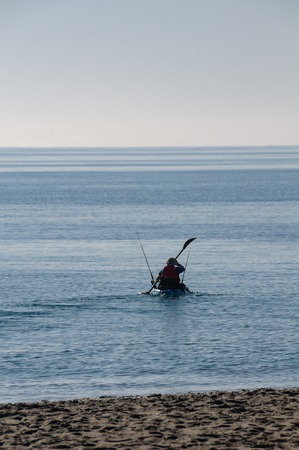 A canoeist with fishing rods paddling on the Mediterranean Sea on a beautiful sunny day with blue sky at the Costa Blanca in Spain. Stock Photo