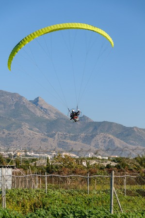 One man flying in front of some mountains with an engine driven yellow paraglider on a sunny day with blue sky and no clouds.