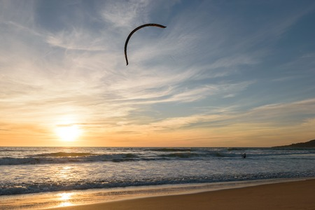 A Kitesurfer going into the Atlantic Ocean at a colorful sunset with his Kite high up in the air in Tarifa, Spain. Stock Photo