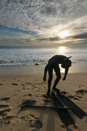 harpoon: A snorkeler with a harpoon standing on a beach at sunset and clouds in the sky in Tarifa, Spain-