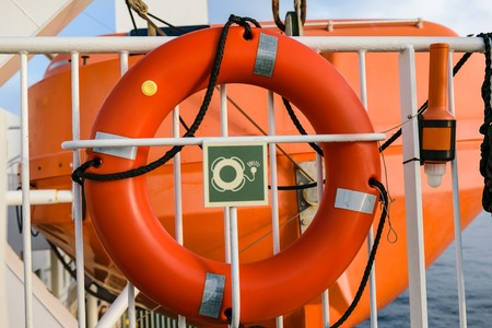 A red lifebelt on a ferry mounted on a fence in front of a lifeboat.