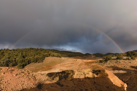 A rainbow and dark clouds in the Ifrane National Park in Morocco.