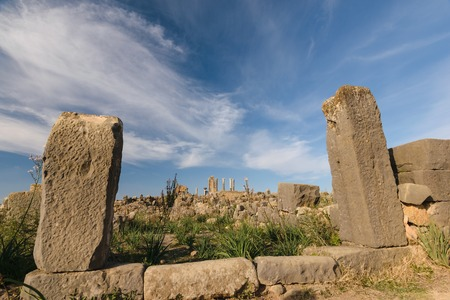 A wall of the roman ruins of Volubilis on a beautiful day with blue sky and only few clouds.