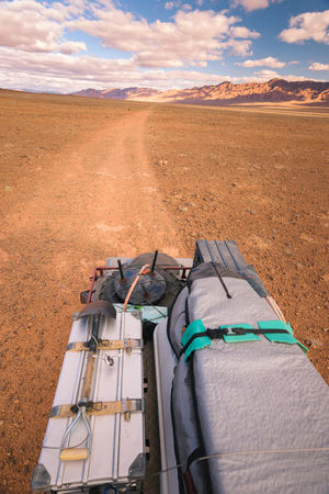 restraint: View from the top of a four by four oldtimer off-road vehicle driving off- road in a desert in Morocco. The vehicle is fully equipped with roof rack  and other off- road items.