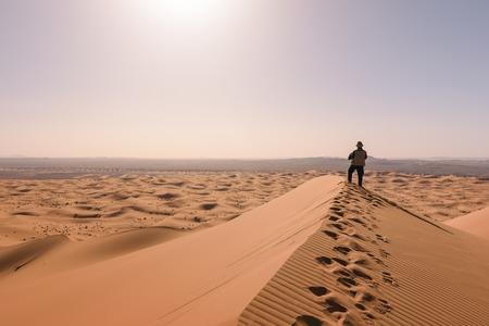 Man overlooks the dunes of Erg Chebbi, Merzouga, Morocco