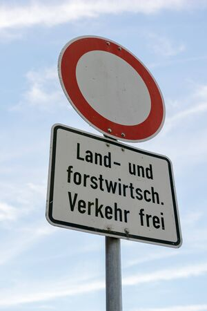 A road sign that says - No thoroughfare - except agricultural and silvicultural traffic in german language in front of blue sky.