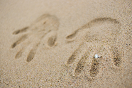 Engagement ring with handprint in sand Stock Photo