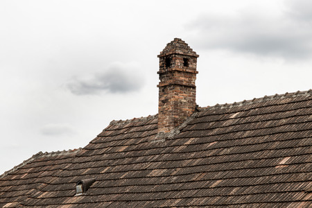 Brick chimney on the roof of old house.  Old roof and tiles. Standard-Bild - 122198870