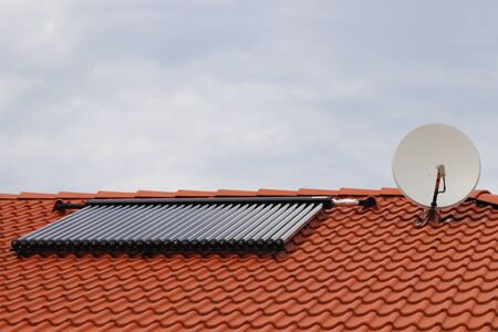 Vacuum collectors - solar water heating system on red roof of the house with satellite. Stock fotó