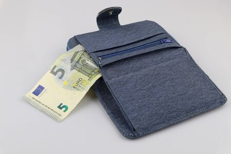 Open blue wallet with 5 euro banknote. Isolated on the white background. Фото со стока