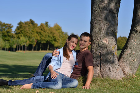 sittting: Young couple sittting under the tree in the parkland Stock Photo