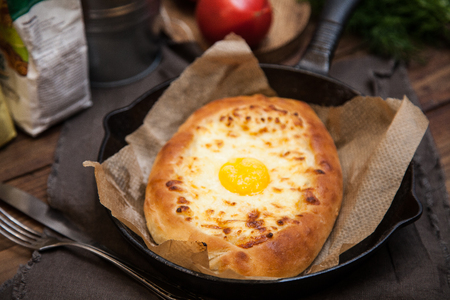 Khachapuri in Adzharian with yolk. Georgian national cuisine. Stock Photo
