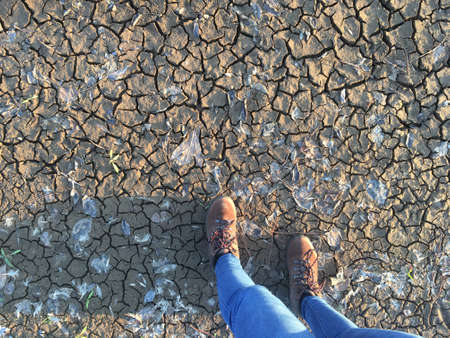 Soil overhead with desertification, drought, woman legs in jeans and field boots, copy space Stock Photo