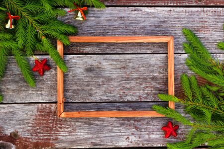 Christmas background for greeting card. wooden frame and Fir branches on wooden background.