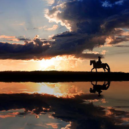 Horseback riding on coastline on sunset   Stock Photo
