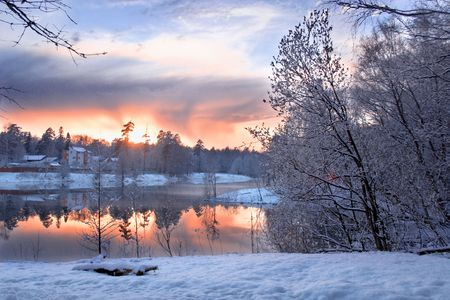Winter evening landscape with lake and forest